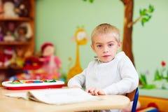 El muchacho lindo, niño con el special necesita aprender en centro de rehabilitación Fotografía de archivo libre de regalías