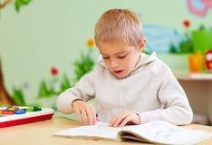 El muchacho lindo, niño con el special necesita mirar un libro, en centro de rehabilitación Imagen de archivo libre de regalías