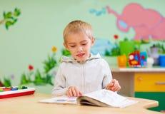 El muchacho lindo, niño con el special necesita mirar un libro, en centro de rehabilitación Imagenes de archivo