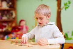 El muchacho lindo, niño con el special necesita solucionar un rompecabezas en centro de rehabilitación Imágenes de archivo libres de regalías