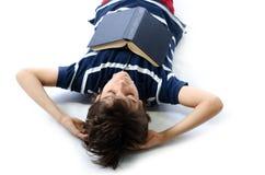 El muchacho lindo se cayó dormido mientras que estudiaba el libro de escuela Imagen de archivo