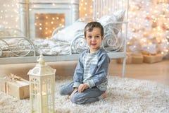 El muchacho lindo se sienta en un piso cerca de la luz Fotografía de archivo