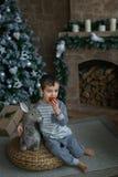 El muchacho lindo sienta y come una manzana cerca de un árbol de navidad fotografía de archivo libre de regalías