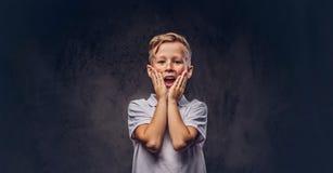 El muchacho lindo sorprendido se vistió en los soportes blancos de una camiseta con las manos en cara en un estudio en la oscurid Imágenes de archivo libres de regalías