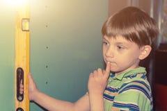El muchacho lleva a cabo el nivel de la construcción, comprobando la exactitud de la pared y pensó en la reparación foto de archivo libre de regalías