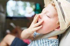 El muchacho lleva a cabo su mano sobre su boca mientras que bosteza imágenes de archivo libres de regalías