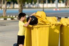 El muchacho lleva la basura en el bolso para elimina al compartimiento Fotografía de archivo libre de regalías