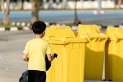 El muchacho lleva la basura en el bolso para elimina al compartimiento Foto de archivo libre de regalías