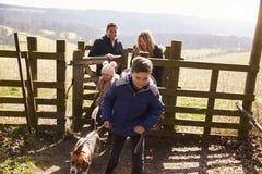 El muchacho lleva su familia y perro a través de una puerta en campo Fotos de archivo libres de regalías