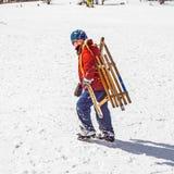 El muchacho lleva su trineo encima de la colina Fotografía de archivo libre de regalías