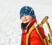 El muchacho lleva su trineo encima de la colina Foto de archivo