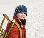 El muchacho lleva su trineo encima de la colina Foto de archivo libre de regalías