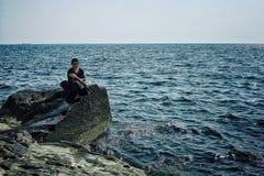 El muchacho local está pescando para la cena en la orilla del mar Caspio en donde las reuniones del desierto y del agua imagen de archivo