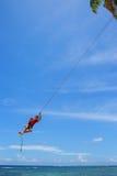 El muchacho local que balancea en un oscilación de la cuerda en el pueblo de Lavena, Taveuni es Imagenes de archivo