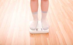 El muchacho mide el peso en escalas del suelo Foto de archivo