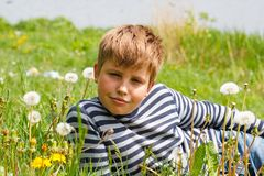 El muchacho miente en hierba cerca del río Fotos de archivo libres de regalías