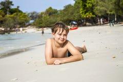 El muchacho miente en la playa arenosa y goza de la arena caliente fina Fotografía de archivo