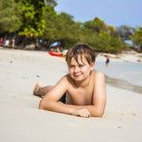 El muchacho miente en la playa arenosa y goza de la arena caliente fina Fotos de archivo libres de regalías