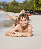 El muchacho miente en la playa arenosa y goza de la arena caliente fina Imagen de archivo libre de regalías