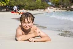 El muchacho miente en la playa arenosa y goza de la arena caliente fina Foto de archivo libre de regalías