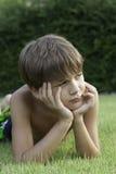 El muchacho miente en un césped Fotos de archivo