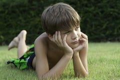 El muchacho miente en un césped Imagen de archivo libre de regalías