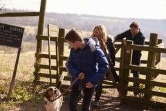 El muchacho mira abajo el perro casero durante paseo de la familia en campo Imagen de archivo