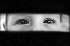 El muchacho mira con miedo a través de la grieta Imágenes de archivo libres de regalías