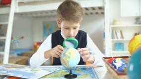 El muchacho mira el globo usando una lupa metrajes