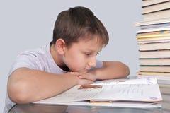 El muchacho mira en una barbilla de reclinación del cuaderno a mano Fotografía de archivo