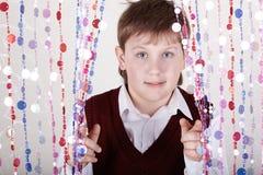El muchacho mira hacia fuera de detrás la cortina Fotografía de archivo