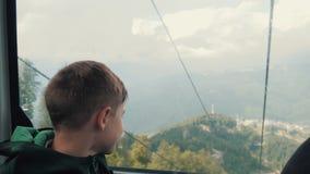 El muchacho mira hacia fuera la ventana del cablecarril Paisaje hermoso, monta?as Viaje lifestyle almacen de video