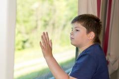 El muchacho mira hacia fuera la ventana en el tren Fotos de archivo libres de regalías