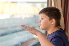 El muchacho mira hacia fuera la ventana en el tren Imagen de archivo