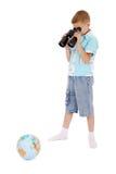 El muchacho mira a través del campo-vidrio el globo Imagen de archivo