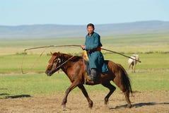 El muchacho mongol del adolescente que lleva el traje tradicional libra en caballo detrás en una estepa en Kharkhorin, Mongolia Imágenes de archivo libres de regalías