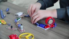 El muchacho monta el circuito eléctrico del constructor almacen de video