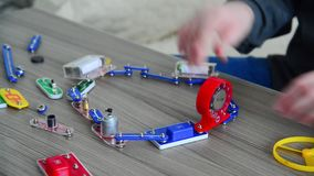 El muchacho monta el circuito eléctrico del constructor almacen de metraje de vídeo