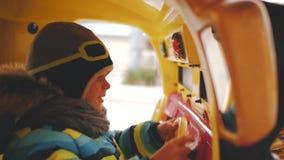 El muchacho monta un coche del juguete en un tiovivo en un casquillo del casco metrajes