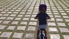 El muchacho monta una bici en el camino de tejas almacen de video