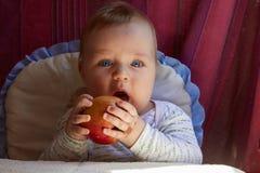 El muchacho muerde la manzana roja grande Imagen de archivo