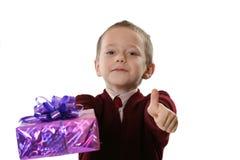 El muchacho muestra el regalo de la Navidad Fotografía de archivo