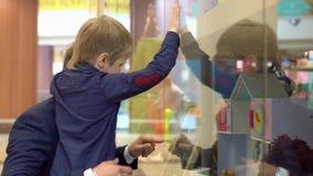 El muchacho muestra en un juguete cuál él quiere para la Navidad El pequeño muchacho de pelo rubio mira la gama de juguetes en ti metrajes