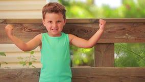 El muchacho muestra sus músculos almacen de metraje de vídeo