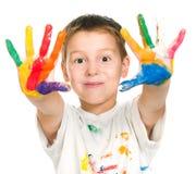 El muchacho muestra sus manos pintadas con la pintura Imagenes de archivo