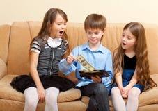 El muchacho muestra una carpeta de dólares a dos muchachas Imágenes de archivo libres de regalías