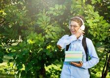 El muchacho muy lindo, joven en vidrios y headphhones redondos y la camisa azul con la mochila sostiene los libros, globo en el p foto de archivo