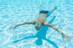 El muchacho nada debajo de cara del agua abajo Imágenes de archivo libres de regalías