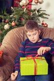 El muchacho no es tan feliz con sus regalos de Navidad imagen de archivo libre de regalías