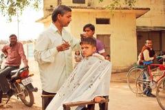 El muchacho no identificado de la edad preescolar corta por el peluquero en la calle entre la gente Foto de archivo